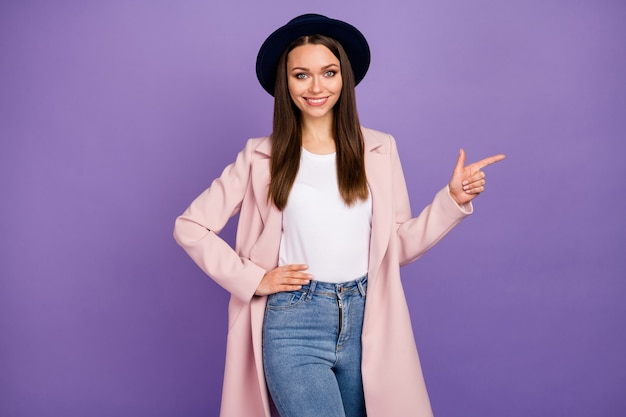 Portrait d'une fille gaie positive en manteau pastel point index copyspace recommande suggérer de sélectionner la promotion de l'annonce porter des vêtements de bonne apparence isolés sur fond de couleur violet