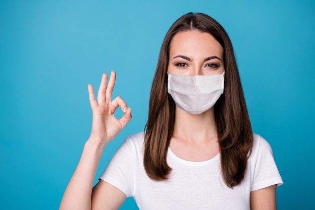 Portrait d'une fille gaie positive montre un signe d'accord sur la quarantaine covid présente la promotion des publicités porte des vêtements de masque médical de bonne apparence isolés sur un fond de couleur bleue