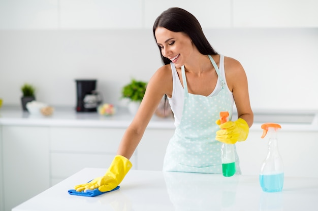 Portrait de fille gaie positive porter du latex de caoutchouc jaune polish bureau à l'aide de détergent sentir contenu dans la cuisine maison lumineuse