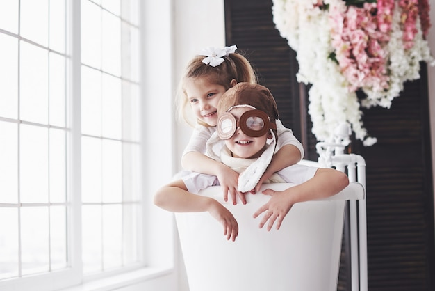 Portrait d'une fille et un garçon au chapeau de pilote jouant dans la salle de bain chez les pilotes ou les marins. voyage, enfance et réalisation de rêves
