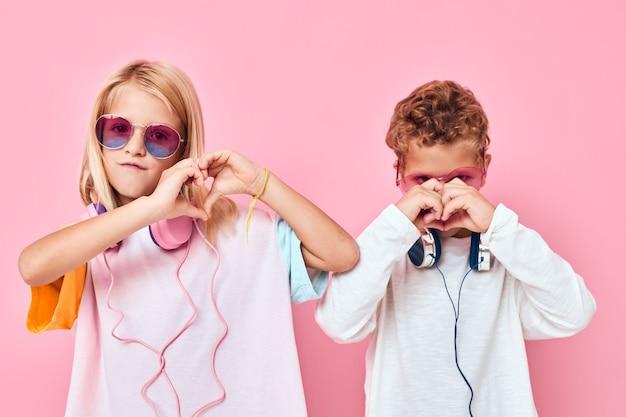 Portrait d'une fille et d'un garçon à lunettes de soleil s'amuser avec des amis en studio posant