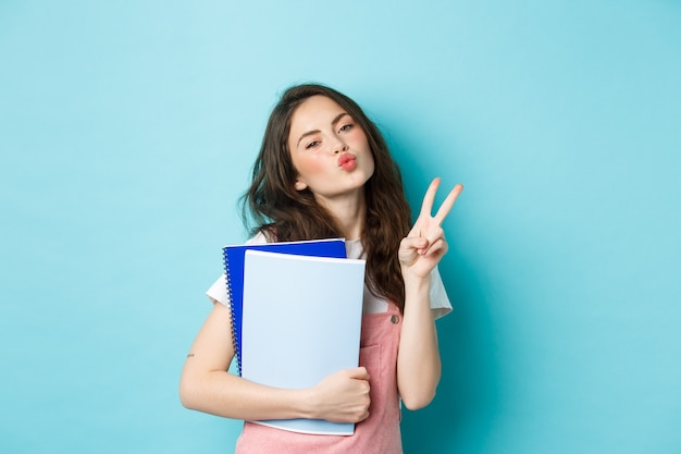 Portrait d'une fille glamour montrant un visage embrassant et un signe v, portez du matériel de devoirs pour les cahiers, debout sur fond bleu