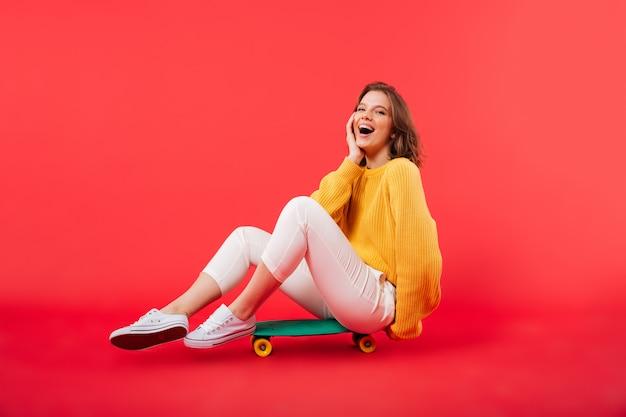 Portrait d'une fille heureuse assise sur une planche à roulettes