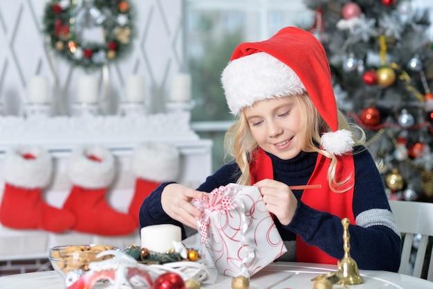 Portrait de fille heureuse en bonnet de noel assis avec cadeau de noël