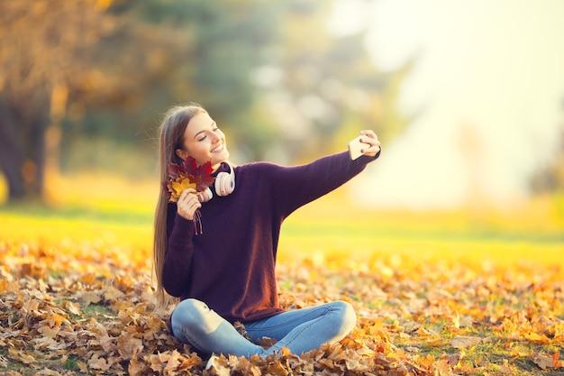 Portrait d'une fille heureuse avec un casque et un smartphone dans un parc d'automne qui écoute de la musique ou fait du selfie