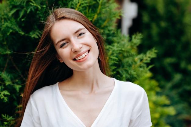 Portrait de fille heureuse de cheveux roux posant en plein air