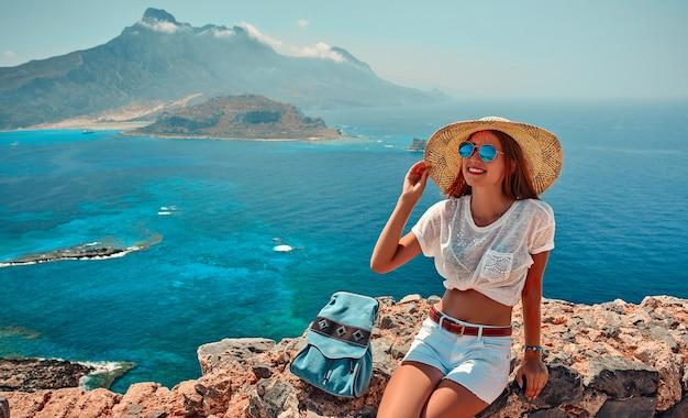 Portrait d'une fille heureuse dans un chapeau, des lunettes de soleil et un sac à dos assis sur fond de montagnes et de mer. notion de tourisme.
