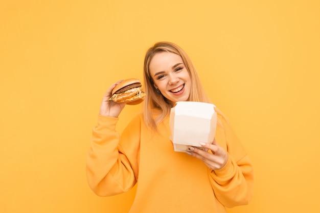 Portrait d'une fille heureuse debout avec des packs blancs et un hamburger dans ses mains sur un jaune