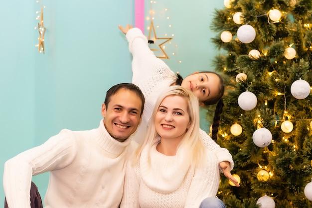Portrait de fille heureuse décorant le sapin de noël. concept de famille, noël, hiver, bonheur et personnes.