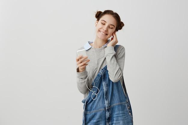 Portrait de fille heureuse et heureuse mettant des écouteurs en profitant de la gaieté seule avec de la musique. jolie femme fermant les yeux de plaisir après avoir reçu les compliments de son mari. émotions humaines