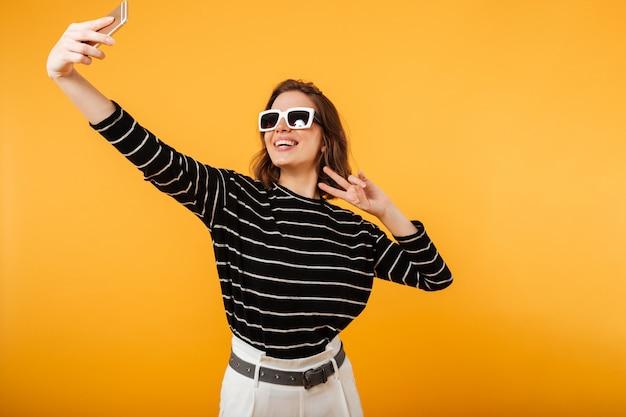 Portrait d'une fille heureuse à lunettes de soleil prenant un selfie