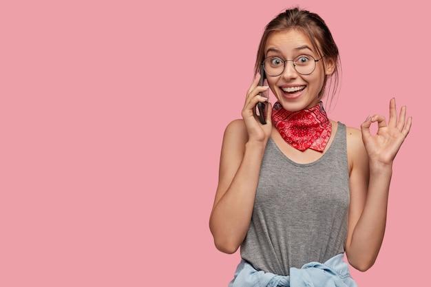 Portrait de fille heureuse parle sur téléphone mobile avec une expression positive, fait un geste correct