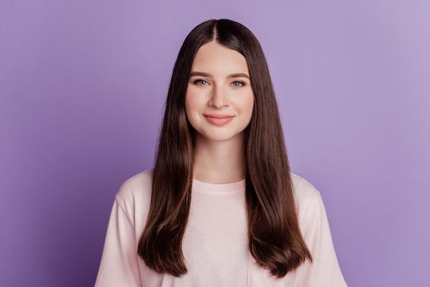 Portrait d'une fille heureuse et positive posant sur fond violet