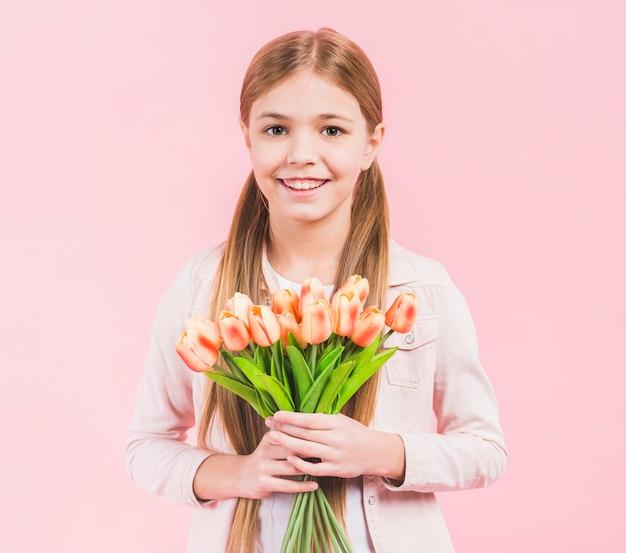 Portrait, fille heureuse, regarder, appareil photo, tenant, bouquet tulipes, debout, main, contre, fond rose