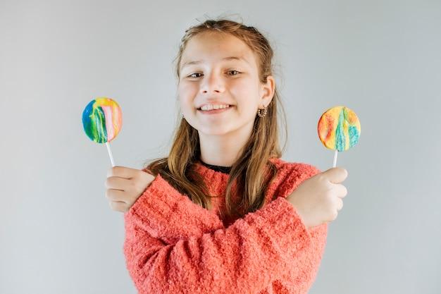 Portrait d'une fille heureuse tenant des sucettes