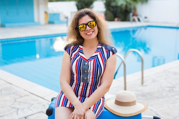 Portrait d'une fille heureuse en vacances d'été contre piscine, robe rayée habillée et lunettes de soleil.