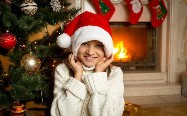 Portrait de fille joyeuse en bonnet de noel assis près de la cheminée brûlante à la maison