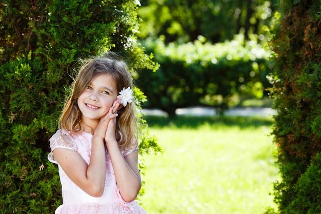 Portrait d'une fille joyeuse dans une robe rose luxuriante dans le parc.