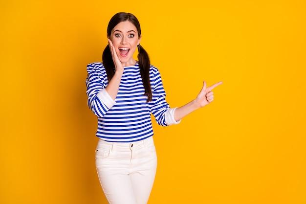 Portrait d'une fille joyeuse étonnée, promoteur de point d'index, copyspace impressionné par la promotion d'annonces incroyables de manière directe, porter un pantalon isolé sur fond de couleur brillante