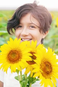 Portrait de fille joyeuse avec des fleurs de tournesol, heure d'été