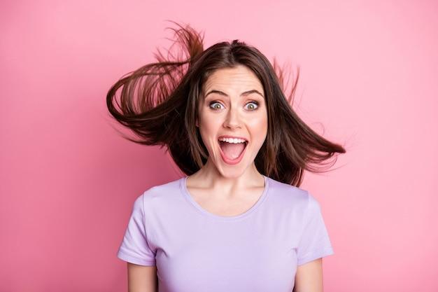 Portrait d'une fille joyeuse positive étonnée impressionnée par une merveilleuse nouveauté d'aubaine crier sa coupe de cheveux à la mouche de l'air porter une tenue violette isolée sur fond de couleur rose