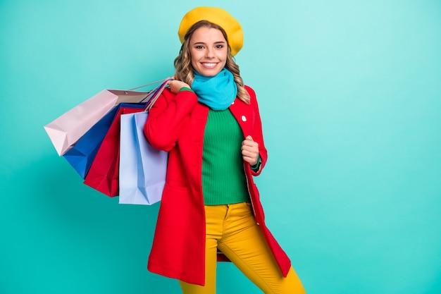 Portrait d'une fille joyeuse et positive profiter du week-end de shopping acheter tenir de nombreux sacs porter des couvre-chefs bleus verts isolés sur fond de couleur turquoise