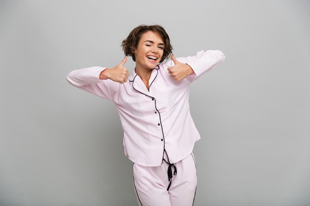 Portrait d'une fille joyeuse en pyjama montrant les pouces vers le haut