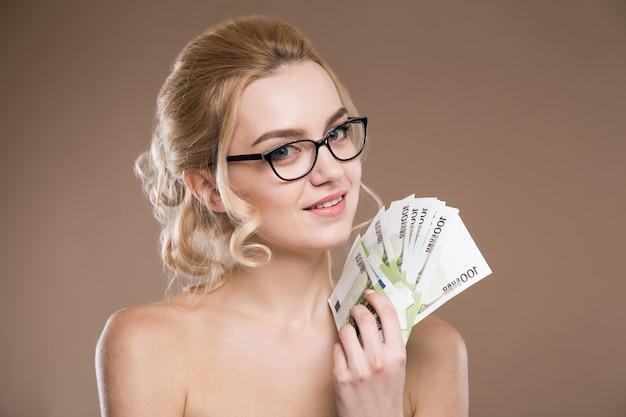 Portrait d'une fille à lunettes avec de l'argent en main