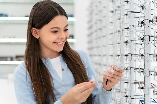 Portrait fille en magasin de lunettes en choisissant la paire
