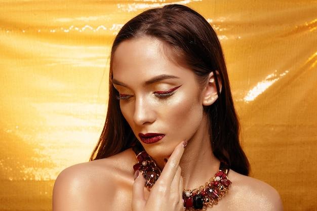 Portrait de fille magique en or. maquillage doré, portrait en gros plan en studio, couleur. beauty model girl avec un maquillage brillant parfait, des lèvres rouges, des bijoux marron doré. maquillage de dame sexy fête de vacances.