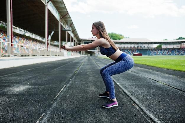 Portrait d'une fille magnifique faisant des squats dans le stade.