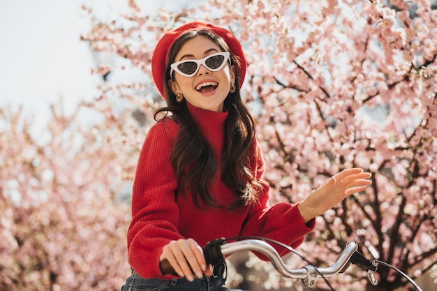 Portrait de fille magnifique en tenue rouge et lunettes de soleil sur fond de sakura. femme joyeuse en pull en cachemire et béret souriant et vélo