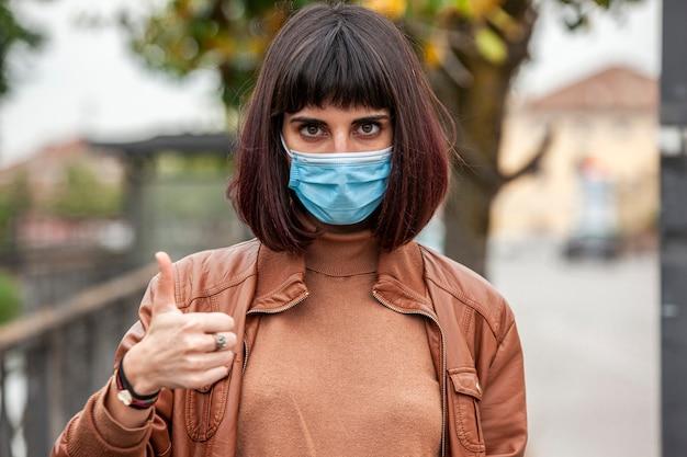 Portrait d'une fille avec un masque médical en plein air pendant la quarantaine covid en italie