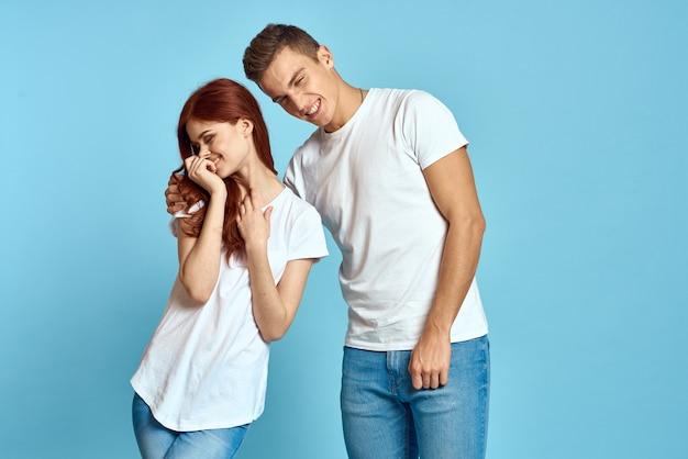 Portrait d'une fille et d'un mec sur un bleu en t-shirts et jeans blancs