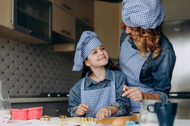 Portrait de fille et mère sont remuer la pâte. concept de famille