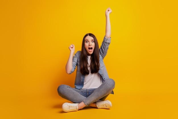 Portrait d'une fille de mode joyeuse s'asseoir au sol, bouche ouverte, célébrer la victoire sur fond jaune