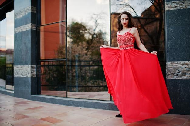 Portrait d'une fille à la mode à la robe de soirée rouge posée fenêtre miroir de fond du bâtiment moderne