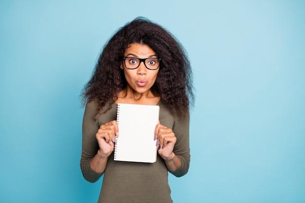 Portrait de fille mulâtre étonné montrer son livre de copie se sentir impressionné émotions porter des lunettes cavalier de style décontracté isolé sur mur de couleur bleu