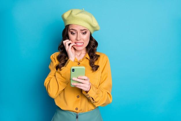 Portrait d'une fille nerveuse utiliser un smartphone lire un horrible réseau social de blogs terribles informations sur le virus corona mordre les ongles porter une chemise jaune couvre-chef isolé fond de couleur bleu