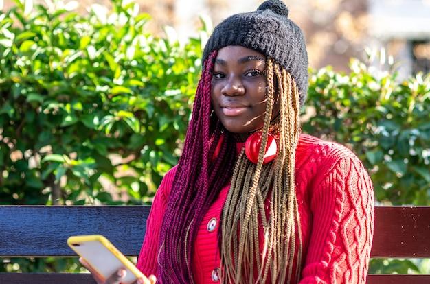 Portrait d'une fille noire avec des tresses colorées assis sur un banc et à l'aide de son téléphone. vêtu d'un pull rouge et d'un bonnet de laine noir.