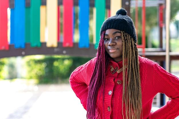 Portrait d'une fille noire avec des tresses colorées dans un parc. vêtu d'un pull rouge et d'un bonnet de laine noir.