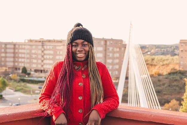 Portrait d'une fille noire avec des tresses colorées. vêtu d'un pull rouge et d'un bonnet de laine noir. pont urbain et bâtiments