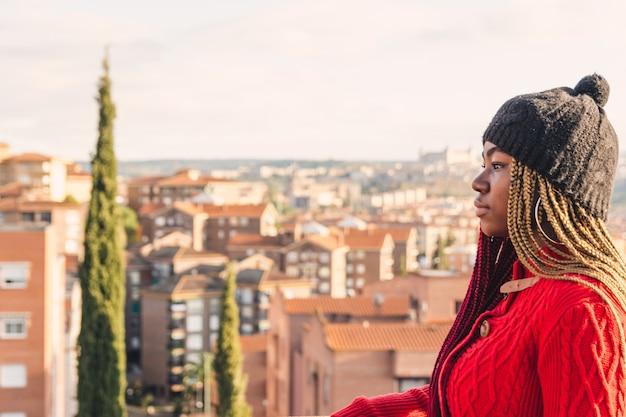 Portrait d'une fille noire avec des tresses colorées. vêtu d'un pull rouge et d'un bonnet de laine noir. vue de la ville