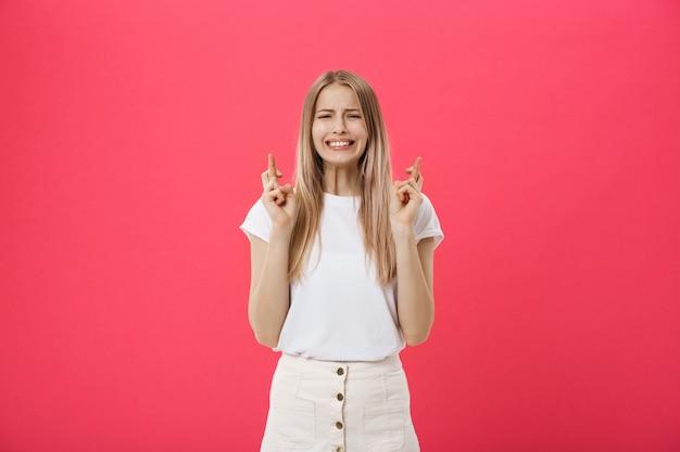 Portrait d'une fille occasionnelle souriante tenant les doigts croisés pour la bonne chance isolé sur fond rose