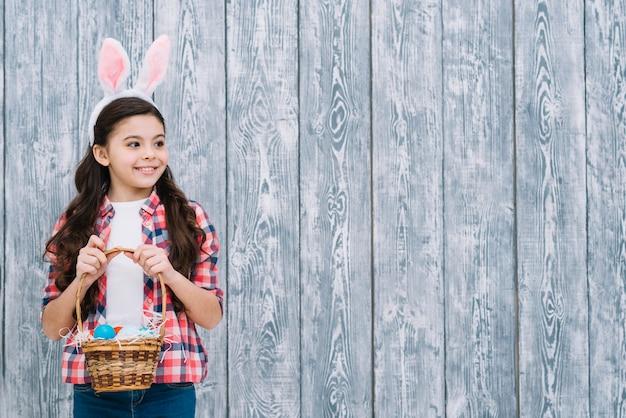 Portrait, fille, oreilles lapin, tenue, panier oeufs pâques, regarder loin