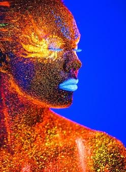 Portrait d'une fille peinte en poudre fluorescente.