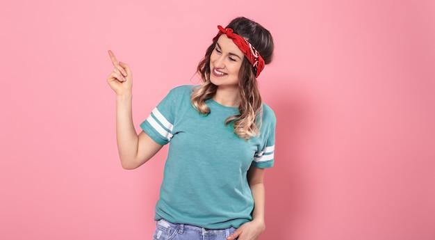Portrait fille pointant son doigt sur le côté sur un mur rose isolé