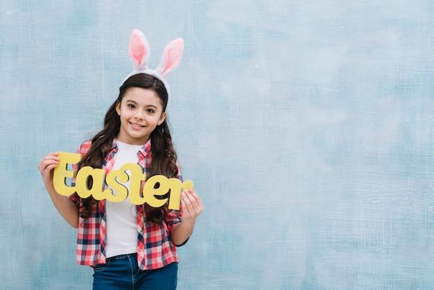 Portrait, fille, porter, oreille lapin, tenue, jaune, mot, paques, debout, contre, mur bleu