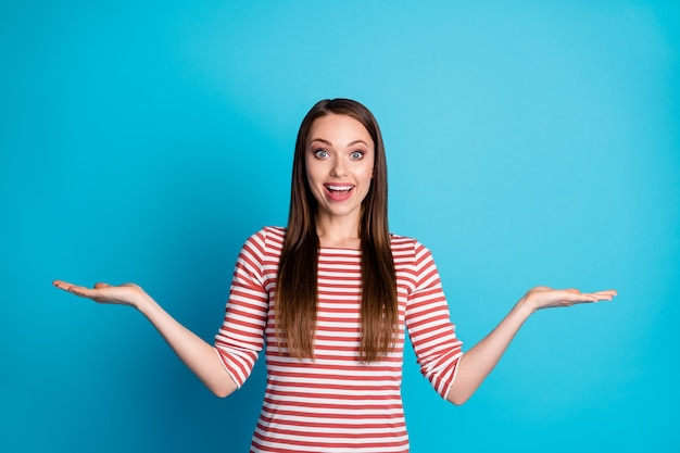 Portrait d'une fille positive choquée, tenir la main pour montrer des publicités incroyables porter de bons vêtements isolés sur fond de couleur bleu