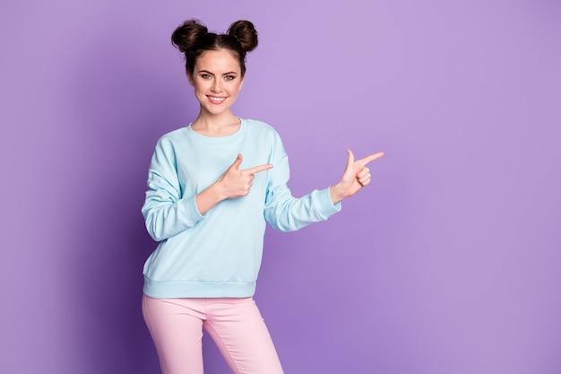 Portrait d'une fille positive et confiante, promoteur pointer du doigt copyspace présenter des annonces de vente promo recommander suggérer de porter un pantalon isolé sur fond de couleur violette
